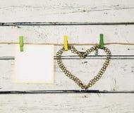 链子的古铜色心脏在一条绳索的与晒衣夹和卡片 库存照片