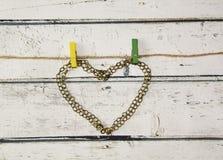 链子的古铜色心脏在一条绳索的与晒衣夹 免版税库存照片