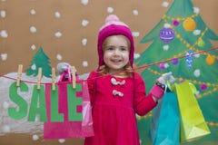 销售、圣诞节、假日和人概念-红色礼服的微笑的婴孩有销售的签字和袋子 图库摄影