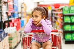 销售、消费者至上主义和人概念-愉快的女孩沉思在手推车 免版税库存照片