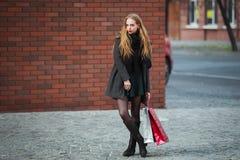 销售、消费者至上主义和人概念-拿着购物袋的愉快的年轻美丽的妇女,轻易地胜过商店 免版税库存图片