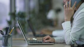 销售主任研究膝上型计算机的在办公室,使用电话的妇女告诉顾客 影视素材
