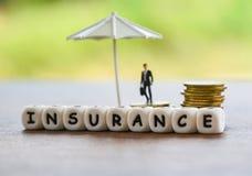 销售保险家、汽车、家庭观念/白色伞保护的金币安全和商人 库存图片