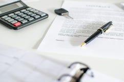 销售合约、钥匙、笔和计算器 免版税库存照片
