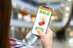 销售和折扣想法,有frameless电话的女孩在被弄脏的购物中心背景 免版税库存照片