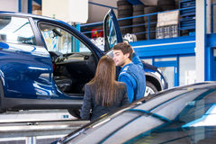 销售技工显示一辆汽车给一个勘察的买家 图库摄影