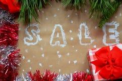 销售的题字在圣诞节背景的 装饰新年度 在牛皮纸 在雪的圣诞节礼物与 免版税库存照片