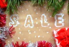 销售的题字在圣诞节背景的 装饰新年度 在牛皮纸 在雪的圣诞节礼物与 库存图片