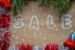 销售的题字在圣诞节背景的 装饰新年度 在牛皮纸 在雪的圣诞节礼物与 免版税图库摄影