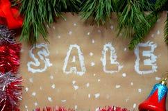 销售的题字在圣诞节背景的 装饰新年度 在牛皮纸 在雪的圣诞节礼物与 库存照片