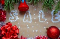 销售的题字在圣诞节背景的 装饰新年度 在牛皮纸 在雪的圣诞节礼物与 免版税库存图片