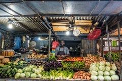 销售立场,卖水果和蔬菜在食物市场上的人  免版税图库摄影