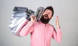 销售额和贴现概念 在销售的人购物晒干,想知道袋子 使上瘾的惊奇的面孔的行家 图库摄影