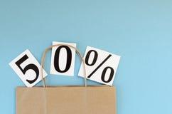 50销售额 在蓝色背景的牛皮纸袋子 免版税库存图片