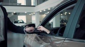 销售主任给客户从汽车的钥匙 免版税库存图片