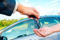 销售主任送钥匙到一辆新的汽车 免版税库存照片