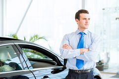 经销商在一辆新的汽车附近站立在陈列室里 库存照片