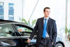 经销商在一辆新的汽车附近站立在陈列室里 免版税库存图片