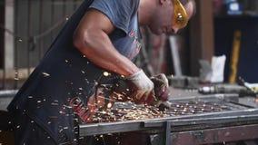锁匠在焊接以后研金属制品使用角度研磨机在伪造商店 影视素材