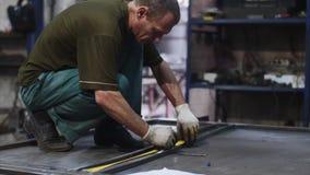 锁匠在车间测量金属棒的卷尺长度并且做标记 股票视频