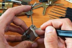 锁匠采摘有lockpick和紧张板钳的一把圆筒锁 免版税库存照片