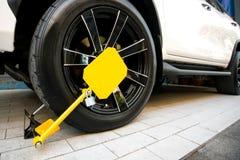 锁有一双特别黄色鞋子的汽车在锁 在一被禁止的停放的锁着的轮子汽车 免版税库存图片