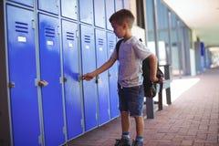 锁衣物柜的男孩,当佩带袋子时 库存图片