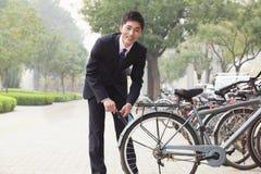 锁他的在一条城市街道上的自行车的年轻微笑的商人在北京,看照相机 库存图片