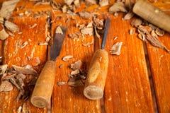 锉和凿子,在桌上的一个雕刻的工具与木裁减片断  库存图片