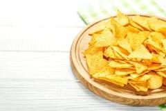 锋利的墨西哥烤干酪辣味玉米片在一个木盘子切削 概念-坏食物, 免版税库存照片