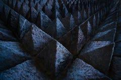 锋利的技巧具体建筑学纹理背景 雕刻在针对性的三角形状的黑暗的石头的独特的样式的艺术图片 图库摄影