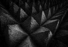 锋利的技巧具体建筑学纹理背景 雕刻在针对性的三角形状的黑暗的石头的独特的样式的艺术图片 免版税图库摄影