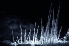 锐利在黑暗的晚上阐明了在雪的冰柱 免版税图库摄影