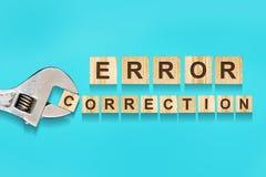 错误校正,在木块写的词,在蓝色背景的可调扳手 查出 错误校正的概念 库存照片