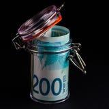 200锡克尔钞票在一个玻璃瓶子的 库存图片