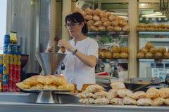 锡切斯,西班牙- 2016年8月21日:摊贩准备薄酥饼rol 免版税库存图片