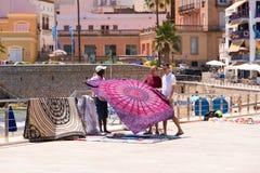 锡切斯, CATALUNYA,西班牙- 2017年6月20日:布料的卖主在沿海岸区的 免版税库存照片