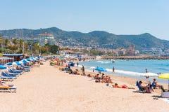 锡切斯, CATALUNYA,西班牙- 2017年6月20日:沙滩的看法 复制文本的空间 查出在蓝色背景 免版税库存图片