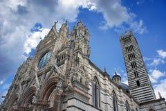 锡耶纳,托斯卡纳,意大利中央寺院。反对明亮的锡耶纳大教堂 免版税库存照片