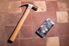 锤击击中智能手机,打破的触摸屏玻璃慢动作急流的崩溃 碎片片段 库存图片