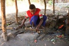 锤击和创造游人的铁匠男孩纪念品 库存图片