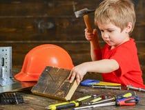 锤击在木板的逗人喜爱的孩子钉子 小安装工在车间 做体力劳动的白肤金发的男孩 免版税库存照片