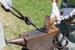 锤击在金属宿营的铁匠说谎在铁砧 免版税库存图片