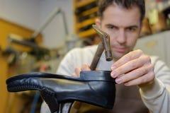 锤击在鞋子的鞋匠在车间 免版税库存图片