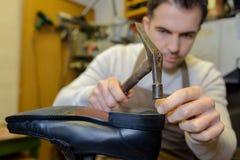 锤击在鞋子的鞋匠在车间 图库摄影