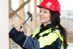 锤击木头的微笑的女性木匠在站点 免版税库存图片