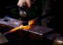 锤击热金属的锻工 免版税库存图片