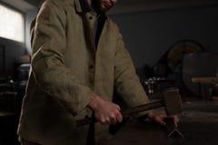 锤击金属零件的男性工作者播种的射击 库存照片
