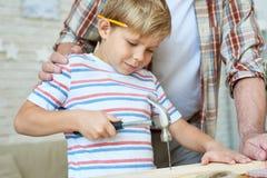 锤击钉子的小男孩 免版税库存图片
