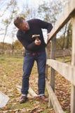 锤击钉子的成熟人入被修理的篱芭 免版税库存图片